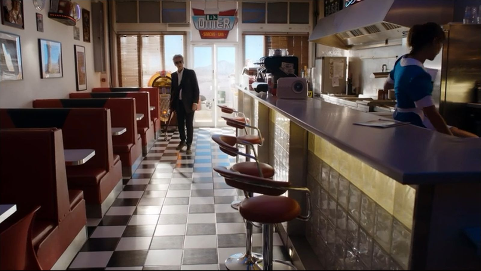 Amy River and Rory arrive at the diner. There is a young black man manning the place. Above the door is a large round circle with an Exit sign. & Doctor Who Diner Inconsistencies | geoffgould.net